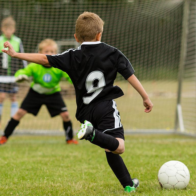 Kind beim Fussball spielen